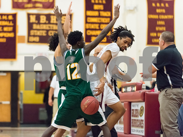 01/15/18 Wesley Bunnell | Staff New Britain High School boys basketball was defeated 53-52 by New London on Monday evening. Jahfari Newman (42) bounces the ball off a defender as he is double teamed along the sideline.