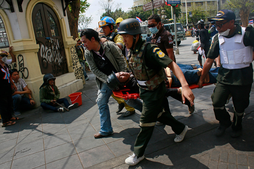 . An injured anti-government protester is carried away by medics during clashes in Bangkok, Thailand, Tuesday, Feb. 18, 2014.  (AP Photo/Wally Santana)