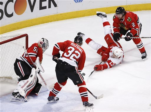 . Detroit Red Wings center Pavel Datsyuk (13) gets a shot on goal while laying on the ice as Chicago Blackhawks goalie Corey Crawford (50) Michal Rozsival (32) and Duncan Keith (2) defend during the second period of an NHL hockey game Wednesday, Feb. 18, 2015, in Chicago. (AP Photo/Charles Rex Arbogast)