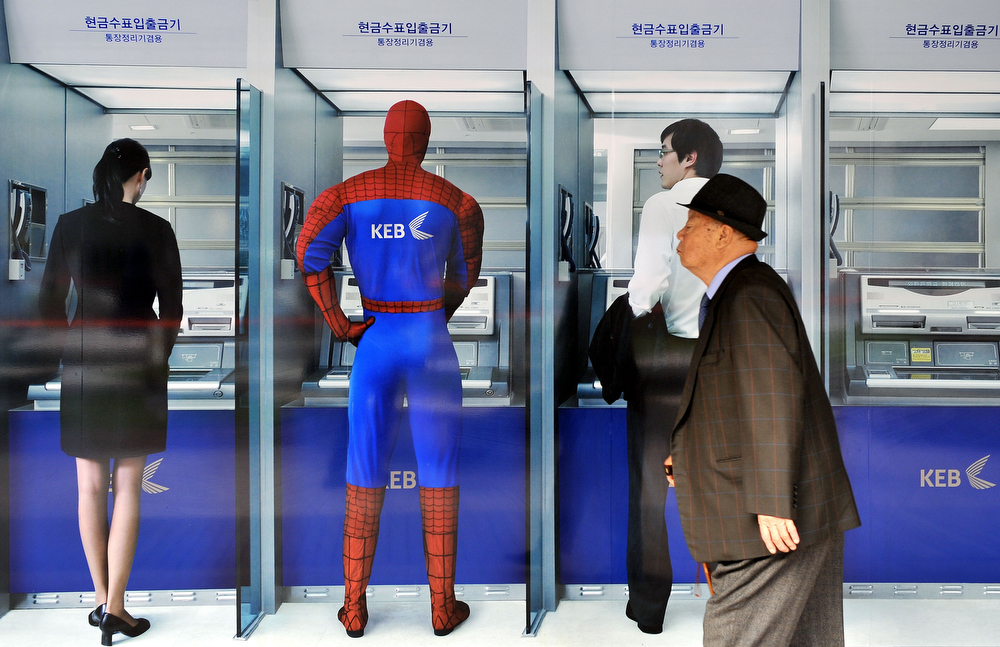 Description of . A South Korean elderly walks past an advertisement for the Korea Exchange Bank at its main building in Seoul on November 24, 2008. The Seoul Central District Court cleared local officials of wrongdoing in the 2003 sale of Korea Exchange Bank to US equity fund Lone Star, saying there was no conspiracy to dispose of it at a fire-sale price. AFP PHOTO/JUNG YEON-JE