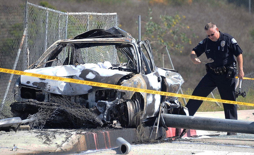 . LAPD do their investigation at the scene were a car crashed into a traffic light pole and burst into flames Friday morning in Porter Ranch, burning one person to death and critically injuring the driver who died later at the hospital and another who escaped from the car The crash on Rinaldi Street near Mason Avenue happened just after 10 a.m. No other vehicles appeared to be involved in the crash. The car was going at a high rate of speed down Rinaldi St. and swerved  to miss another car that was going slower and lost control and hit the traffic light poll and burst into flames. Porter Ranch California, March 29,2013 PHOTO BY Gene Blevins/LA DailyNews