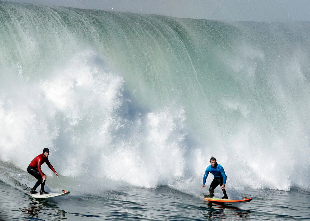Description of . Tyler Smith, left, and Ryan Seelbach ride a wave together during heat 3 of the Mavericks Invitational big wave surf contest in Half Moon Bay, Calif., Sunday, Jan. 20, 2013. (AP Photo/Marcio Jose Sanchez)