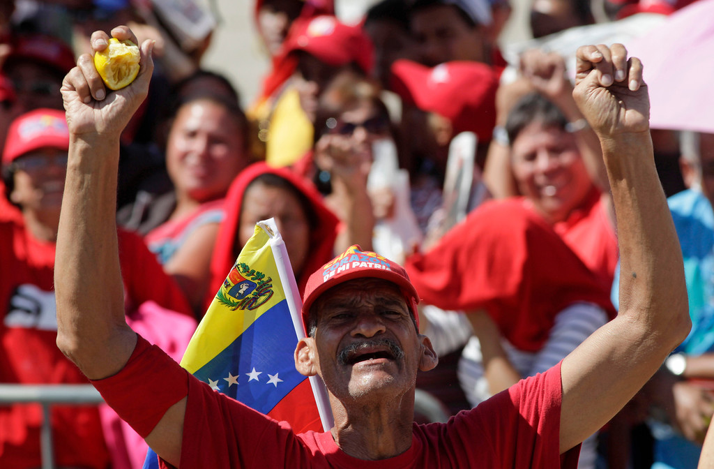 . A man gestures as he watches on a giant screen the funeral ceremony for Venezuela\'s late President Hugo Chavez outside the military academy in Caracas, Venezuela, early Friday, March 8, 2013. (AP Photo/Ariana Cubillos)