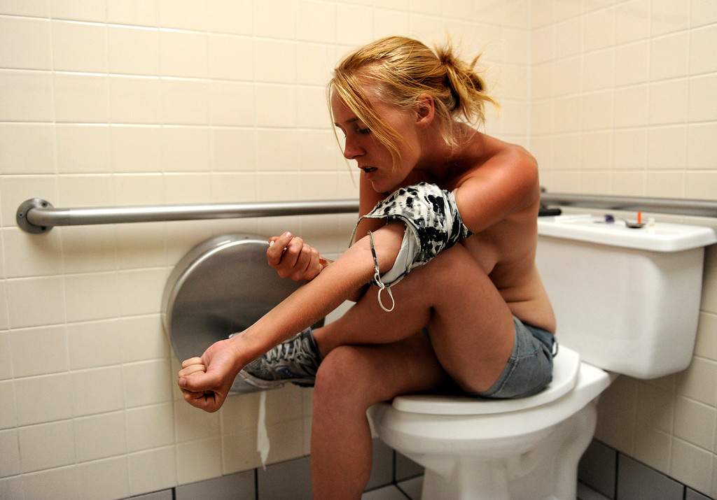 . Alice, 21, and her boyfriend, Iris, have been shooting up heroin while living on the streets of Denver for the past three years. She prefers shooting up in places where you can close and lock a door like this Taco Bell bathroom near downtown Denver. Alice forgot her belt and uses her tank top to tie off her arm. She and Iris made enough quick money for a bag each and after getting high will fly their signs again to make money for their afternoon and morning shots.
