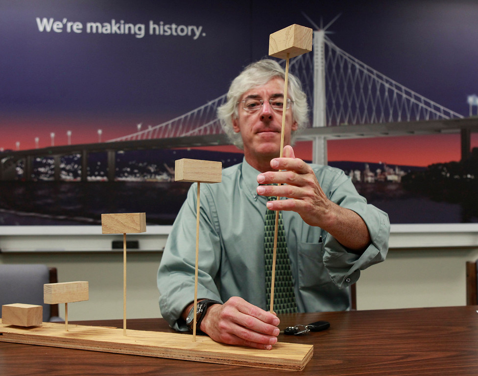 . Caltrans principal bridge engineer Brian Maroney uses a simple wooden block and dowel model Tuesday July 2, 2013 in Oakland, Calif., to demonstrate the effect of multi-dimensional seismic waves that engineers now design for. Maroney is preparing to deliver a side-by-side comparison of the old and new eastern spans of the Bay Bridge to Bay Area legislators on Monday and county and city officials on Wednesday. (Karl Mondon/Bay Area News Group)