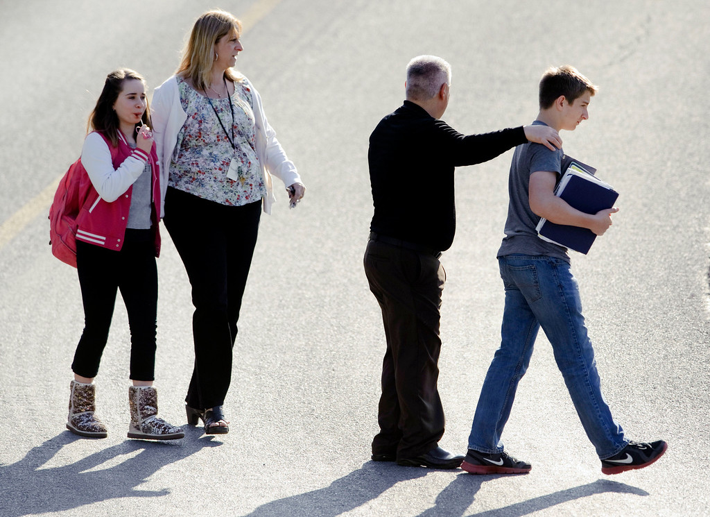 . Students and guardians walk to their car from the Franklin Regional Middle School after more then a dozen students were stabbed by a knife wielding suspect at Franklin Regional High School on Wednesday, April 9, 2014, in Murrysville, Pa., near Pittsburgh. The suspect, a male student, was taken into custody and is being questioned. (AP Photo/Tribune Review, Brian F. Henry)