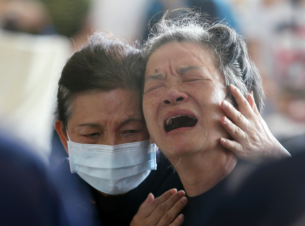 . A relative, right, of a victim in the multiple explosions from an underground gas leak is consoled at a funeral parlor in Kaohsiung, Taiwan, Friday, Aug. 1, 2014. A series of explosions about midnight Thursday and early Friday ripped through Taiwan\'s second-largest city, killing scores of people, Taiwan\'s National Fire Agency said Friday. (AP Photo)