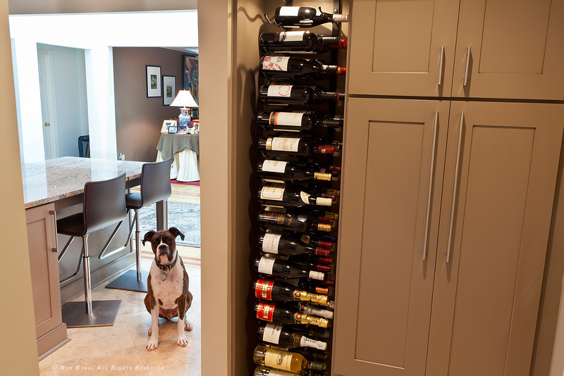 Custom wine rack with plenty of cabinetry for storage. *Enzo not included. Laundry room with additional storage and attached two-car garage located off kitchen, just to the right.