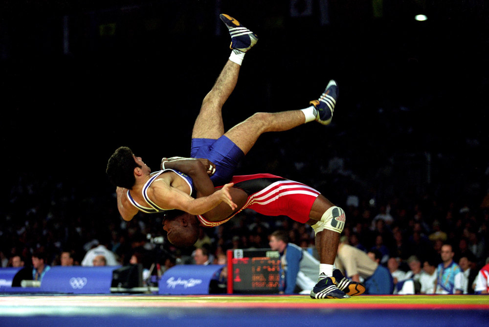 Description of . Ali Abdo of Australia and Filiberto Azcuy of Cuba in action during the Men's 69kg Greco Roman Wrestling held at the Sydney Convention Centre during the Sydney 2000 Olympics, Sydney, Australia. Scott Barbour/ALLSPORT