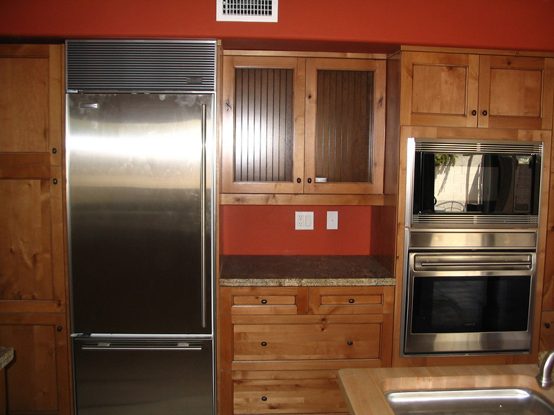 The wall of cabinets with the refrigerator, microwave and oven.