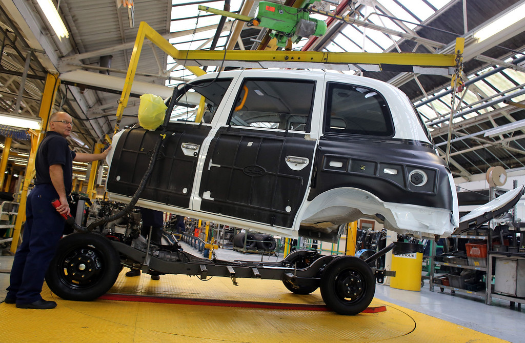 . Workers inside the factory of The London Taxi Company attach the body of a TX4 (Euro 5) London Taxi to its chassis on September 11, 2013 in Coventry, England.   (Photo by Matt Cardy/Getty Images)