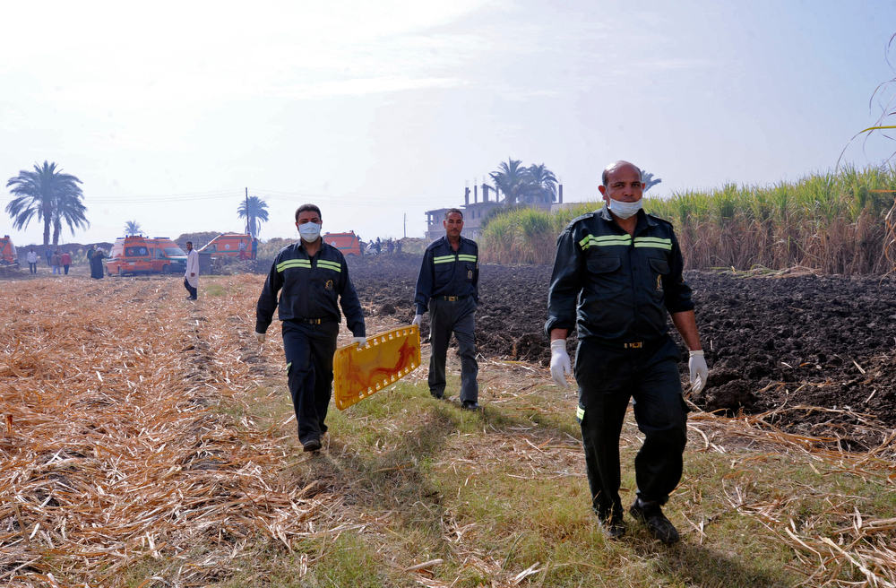 . Rescue workers prepare to remove a body from the scene of a balloon crash outside al-Dhabaa village, just west of the city of Luxor, 510 kilometers (320 miles) south of Cairo, Egypt, Tuesday, Feb. 26, 2013. A hot air balloon flying over Egypt\'s ancient city of Luxor caught fire and crashed into a sugar cane field on Tuesday, killing at least 18 foreign tourists, a security official said. The casualties included French, British, Belgian, Hungarian, Japanese nationals and nine tourists from Hong Kong, Luxor Governor, Saad told reporters. (AP Photo/Hagag Salama)