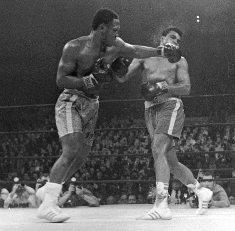 . In this March 8, 1971, file photo, Muhammad Ali. right, takes a left from Joe Frazier during the 15th round of their heavyweight title boxing bout in New York. Frazier won a unanimous decision.   Frazier, the former heavyweight champion who handed Ali his first defeat yet had to live forever in his shadow, died Monday Nov. 7, 2011 after a brief  fight with liver cancer. He was 67. (AP Photo/File)