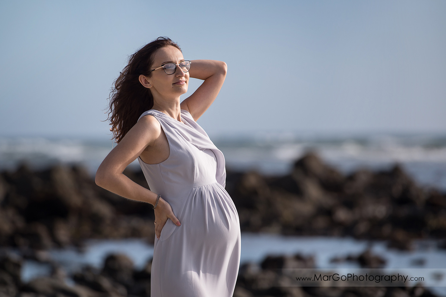 3/4 pose portrait of pregnant woman in gray dress on the Moss Beach during maternity session