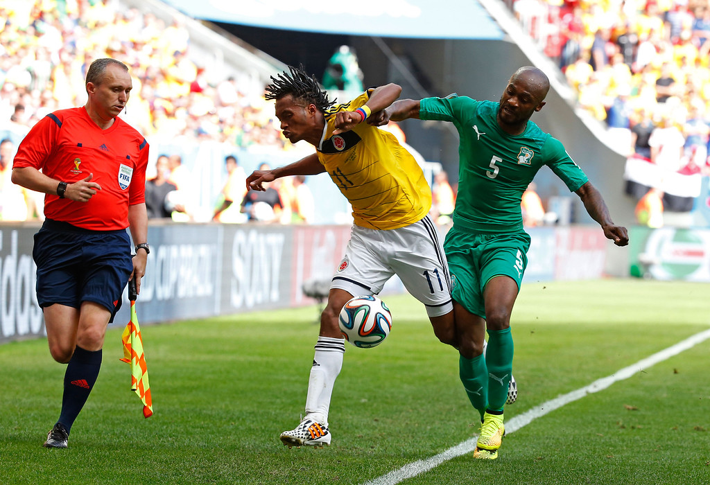 . Didier Zokora of the Ivory Coast competes for the ball with Juan Guillermo Cuadrado of Colombia during the 2014 FIFA World Cup Brazil Group C match between Colombia and Cote D\'Ivoire at Estadio Nacional on June 19, 2014 in Brasilia, Brazil.  (Photo by Gabriel Rossi/Getty Images)