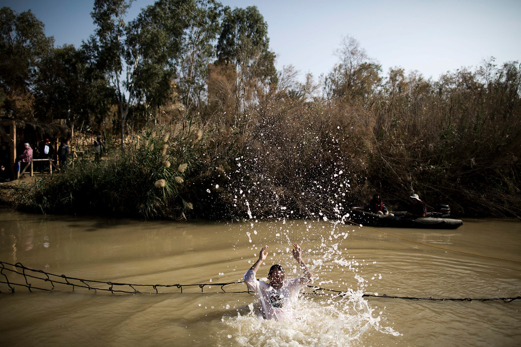 . An Orthodox pilgrim takes a dip in the Jordan River for the baptismal ceremony at the site known as Qasr el-Yahud on the West Bank side of the Jordan River near the city of Jericho, 18 January 2014. Thousands of Orthodox pilgrims flocked to the Jordan River to attend the Epiphany feast celebrations at the traditional site where it is believed Jesus was baptized by John the Baptist.  EPA/ABIR SULTAN