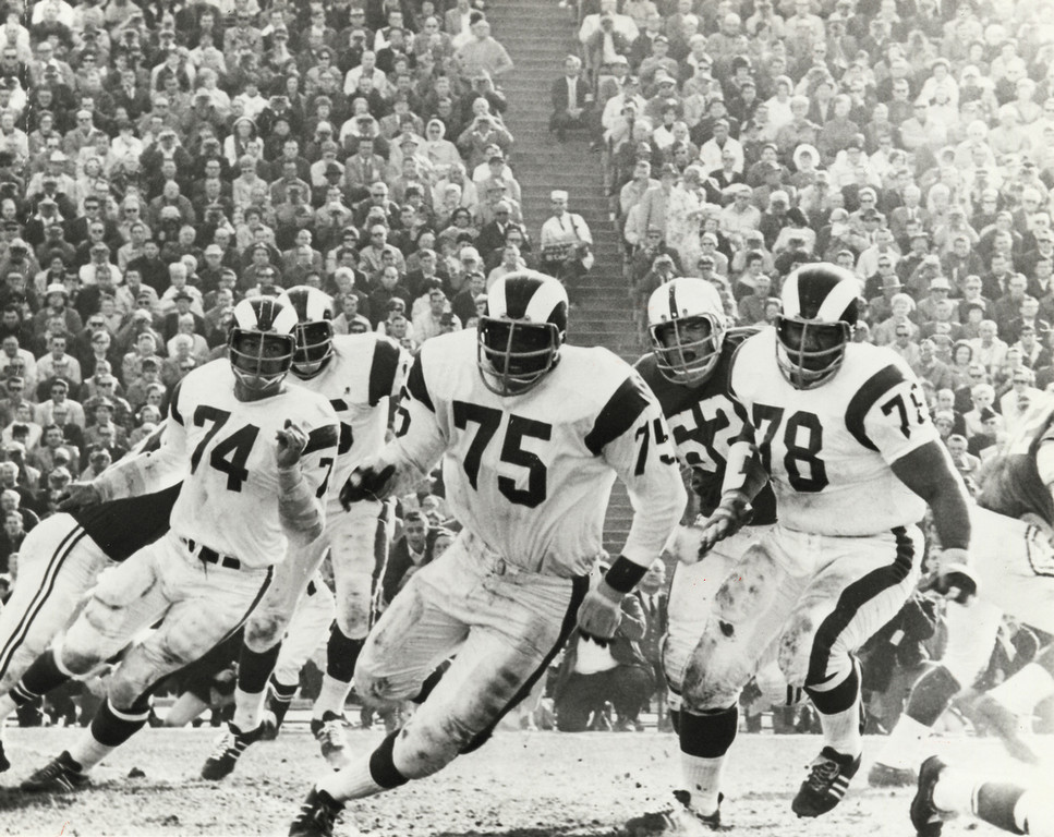 ". In this Dec. 17, 1967 photo provided by NFL Photos, Los Angeles Rams defensive David ""Deacon\"" Jones (75) and defensive tackles Merlin Olsen (74) and Roger Brown (78) battle the Baltimore Colts in Los Angeles.  (AP Photo/NFL Photos)"