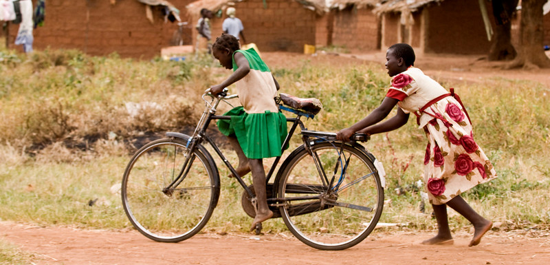 affa's elder sister helping another learn to ride a bike