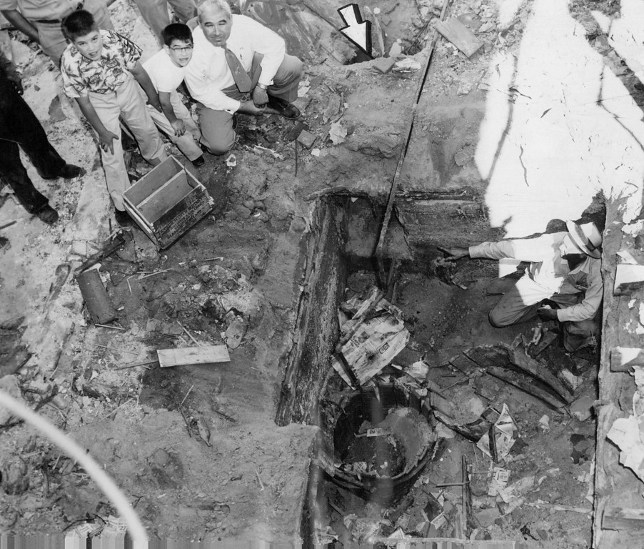 . JUN 10 1954 - Foreman John Strausheim (right) points to a tunnel (arrows) leading into a secret basement room fully equipped as a bootleg whiskey plant. Broken wooden barrels, layers of debris, water and gas lines, a gas stove and The Denver Post for Aug. 27, 1933, were found in the room; which was uncovered by workmen razing a building at 2033 Champa St. Harry Zimmerman, manager of the Champa Linen service, is at left in the white shirt. (Cloyd Teter/ The Denver Post)