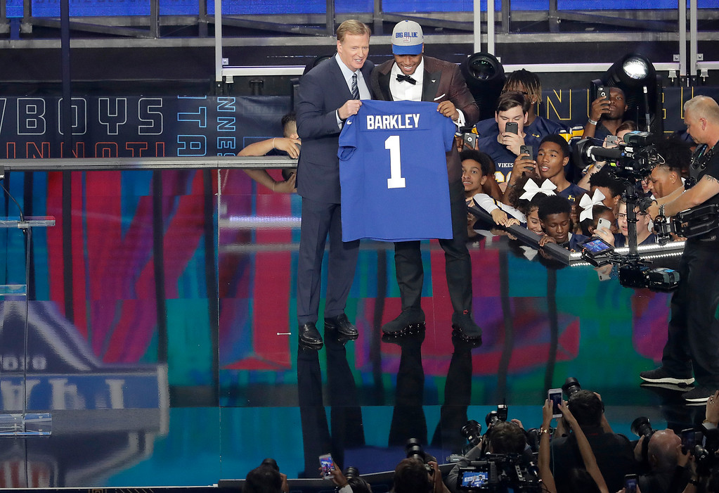 . Commissioner Roger Goodell, left, presents Penn State\'s Saquon Barkley with his New York Giants jersey during the first round of the NFL football draft, Thursday, April 26, 2018, in Arlington, Texas. (AP Photo/Eric Gay)