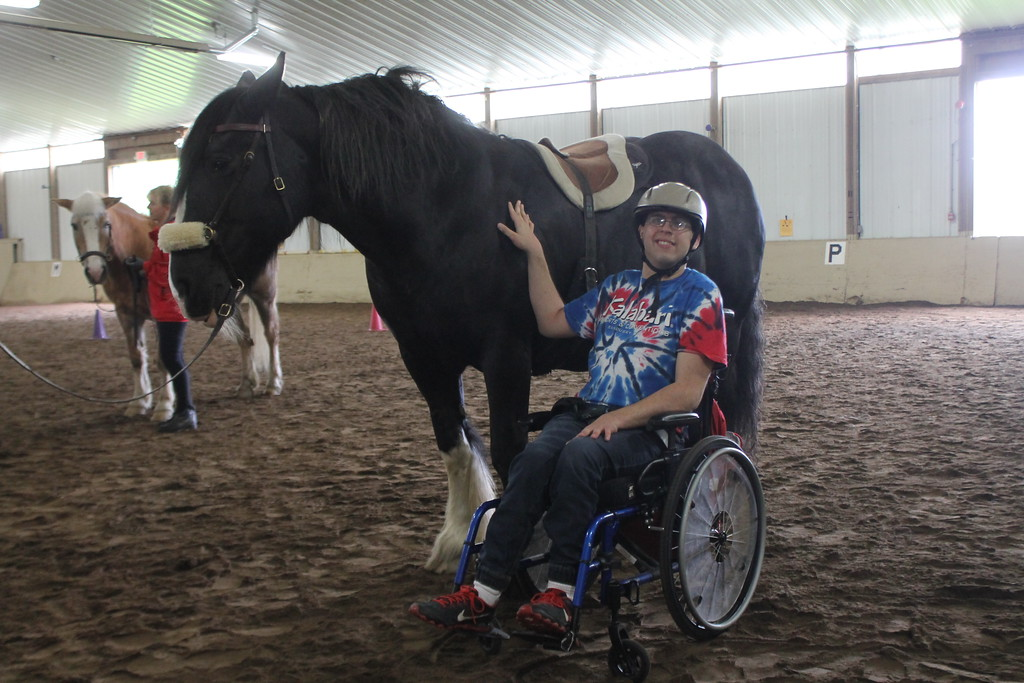 . Brian Posey a client at the Willoughby Branch pets  the horse he rode during an equine therapy exercise at Fieldstone Farm . Kristi Garabrandt - The News-Herald