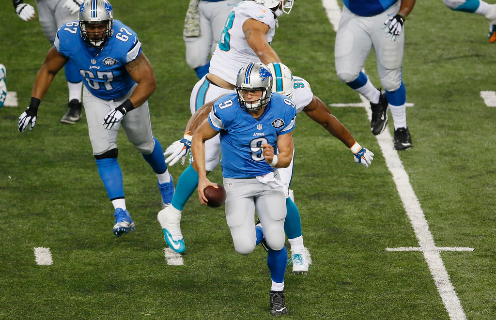 . Detroit Lions quarterback Matthew Stafford (9) scrambles away from Miami Dolphins defensive end Cameron Wake during the first half of an NFL football game in Detroit, Sunday, Nov. 9, 2014. (AP Photo/Paul Sancya)