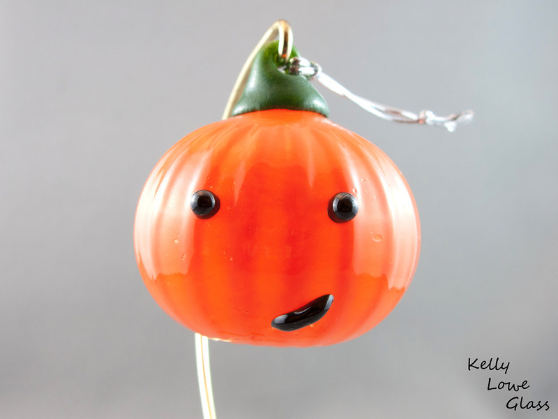 """Jack-o'-lantern (Blown Glass):  A seasonal piece made for my October 2010 showing, these jack-o-lanterns added a fun atmosphere to the studio and were a blast to make. I've since decided to continue making them for future Halloweens.  Height - Approx 7.5cm (3"""") Width - Approx 7cm (2.75"""") Weight: Approx 78g (0.17 lbs)  *Brass hanger in pictures is not included  Please note: as each piece begins its life as molten glass and is blown/sculpted by hand into the final product, individual pieces might have slight variations in size and/or appearance. Please rest assured however that the standard of quality is quite high, and no substandard pieces will be sold."""