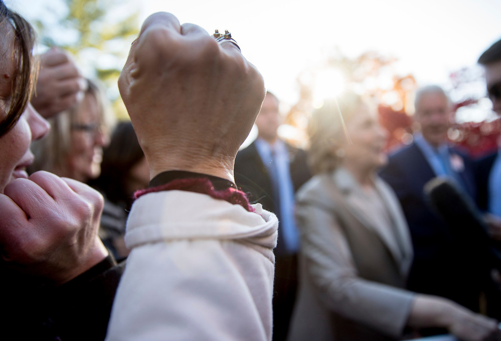 . A supporter raises a fist as Democratic presidential candidate Hillary Clinton speaks to a member of the media outside Douglas G. Grafflin School in Chappaqua, N.Y., Tuesday, Nov. 8, 2016, after voting. (AP Photo/Andrew Harnik)
