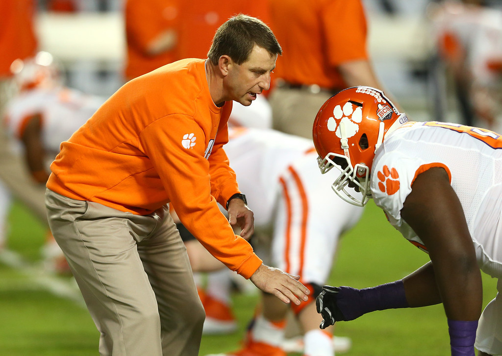 . MIAMI GARDENS, FL - JANUARY 03:  Head coach Dabo Swinney of the Clemson Tigers warms up with his players prior to the Discover Orange Bowl against the Ohio State Buckeyes at Sun Life Stadium on January 3, 2014 in Miami Gardens, Florida.  (Photo by Streeter Lecka/Getty Images)