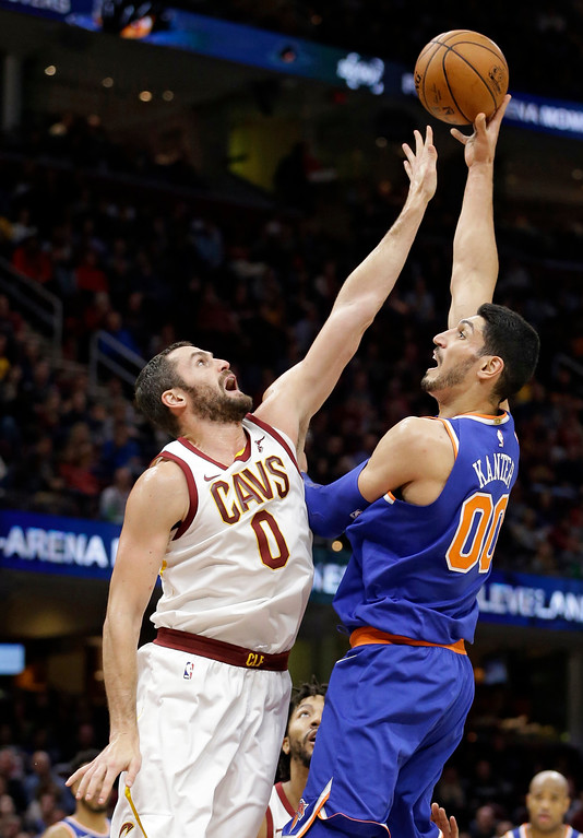 . New York Knicks\' Enes Kanter (00) shoots over Cleveland Cavaliers\' Kevin Love (0) in the second half of an NBA basketball game, Sunday, Oct. 29, 2017, in Cleveland. The Knicks won 114-95. (AP Photo/Tony Dejak)