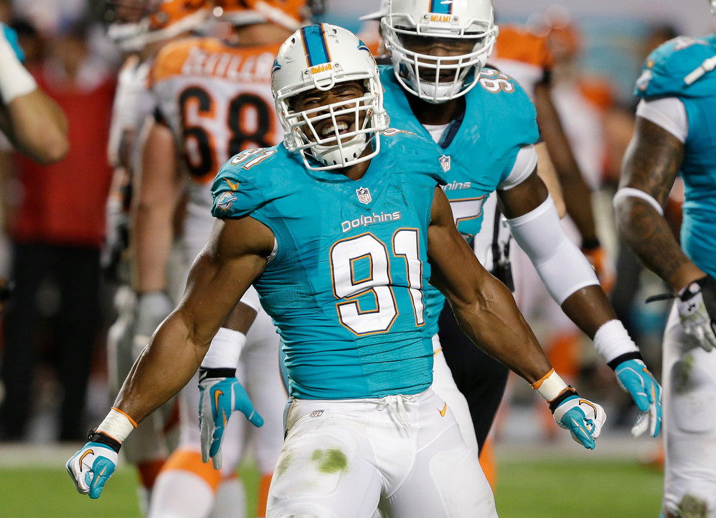 . Miami Dolphins defensive end Cameron Wake celebrates after he recovered a fumble by Cincinnati Bengals quarterback Andy Dalton during the first half of an NFL football game, Thursday, Oct. 31, 2013, in Miami Gardens, Fla. (AP Photo/Wilfredo Lee)