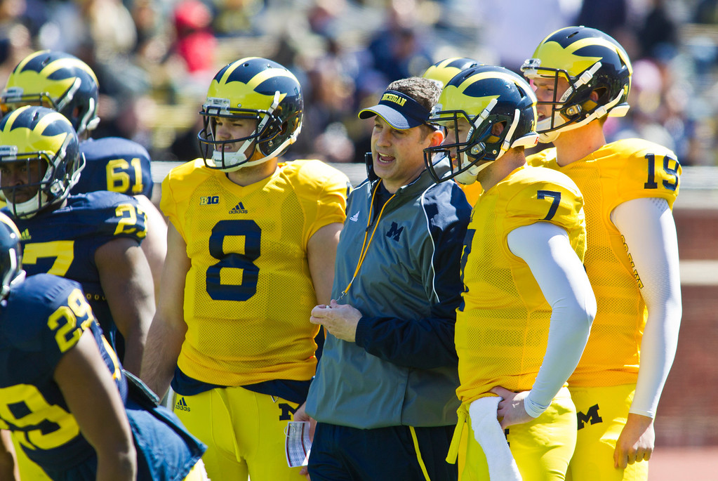 . Michigan offensive coordinator Doug Nussmeier, center, has words with quarterback Shane Morris (7), with quarterbacks Russell Bellomy (8) and Wilton Speight (19) standing by, during the football team\'s annual spring game, Saturday, April 5, 2014, in Ann Arbor, Mich. (AP Photo/Tony Ding)