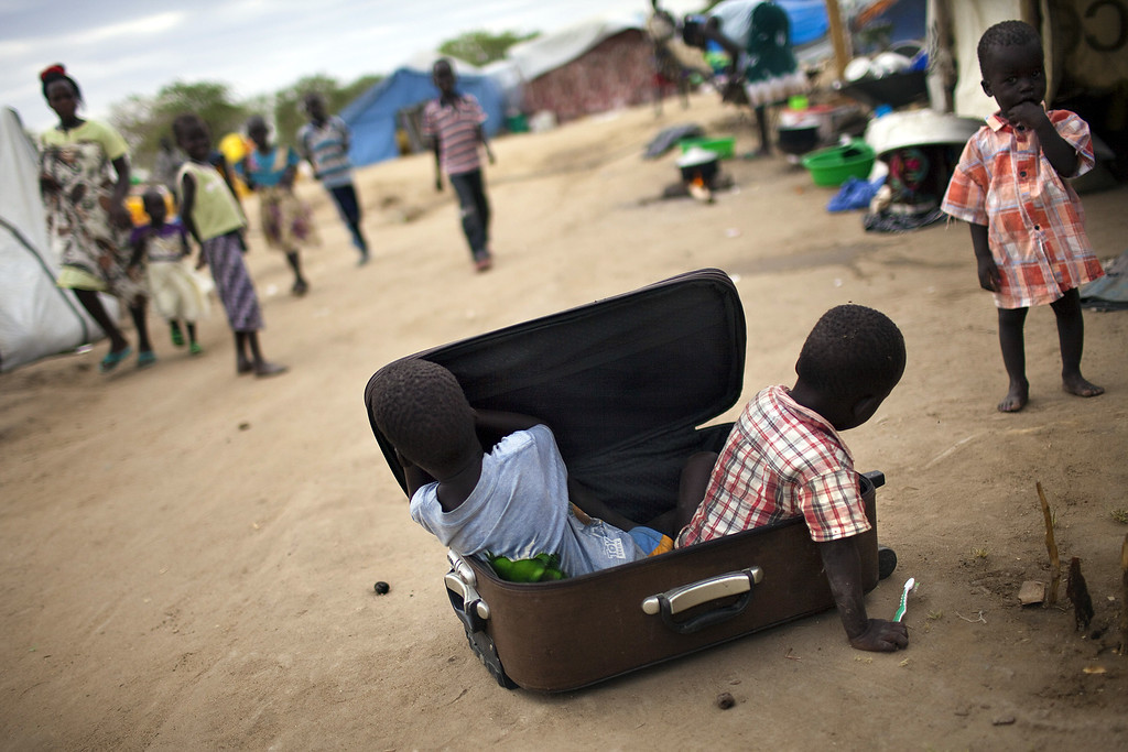 . Children play with a suitcase in a IDP camp for the Nuer ethnic group inside the UNMISS compound in Bor, South Sudan, on February 27, 2014. AFP PHOTO / JM LOPEZ/AFP/Getty Images