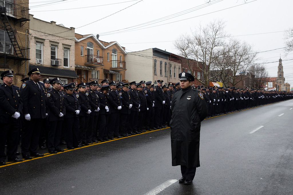. A single police officer turns her back as Mayor Bill de Blasio speaks during the funeral of New York Police Department Officer Wenjian Liu at Aievoli Funeral Home, Sunday, Jan. 4, 2015, in the Brooklyn borough of New York. Liu and his partner, officer Rafael Ramos, were killed Dec. 20 as they sat in their patrol car on a Brooklyn street. The shooter, Ismaaiyl Brinsley, later killed himself. (AP Photo/John Minchillo)
