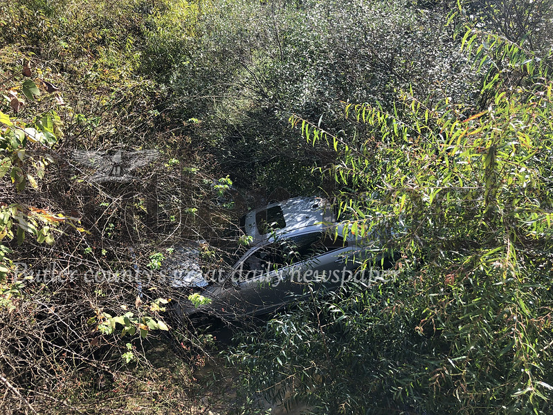 Photo by J.W. Johnson Jr.A vehicle rests after going over embankment Thursday on Franklin Road in Cranberry Township.