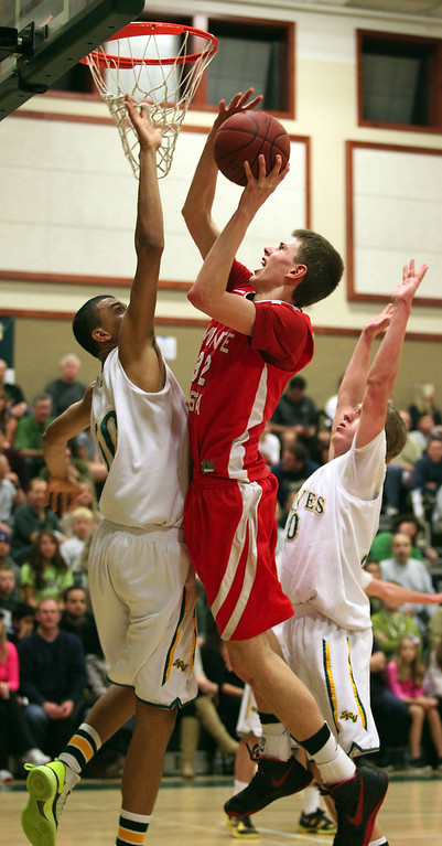 . Monte Vista\'s Spencer Rust (32), center, shoots against San Ramon Valley\'s Gregg Polosky (50), left, and Jet Reed (30), right, in the second half of their varsity boys basketball game in Danville, Calif., on Friday, Feb. 15, 2013. (Anda Chu/Staff)