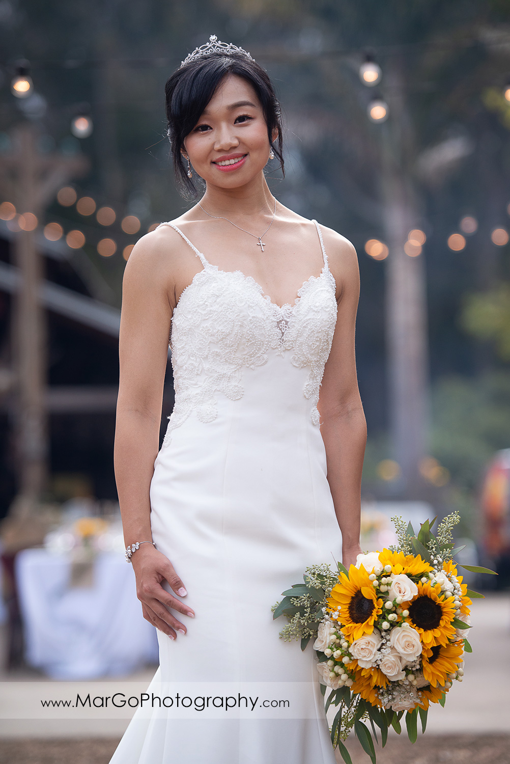 3/4 portrait of the bride in white dress with yellow flower bouquet at Long Branch Saloon & Farms in Half Moon Bay