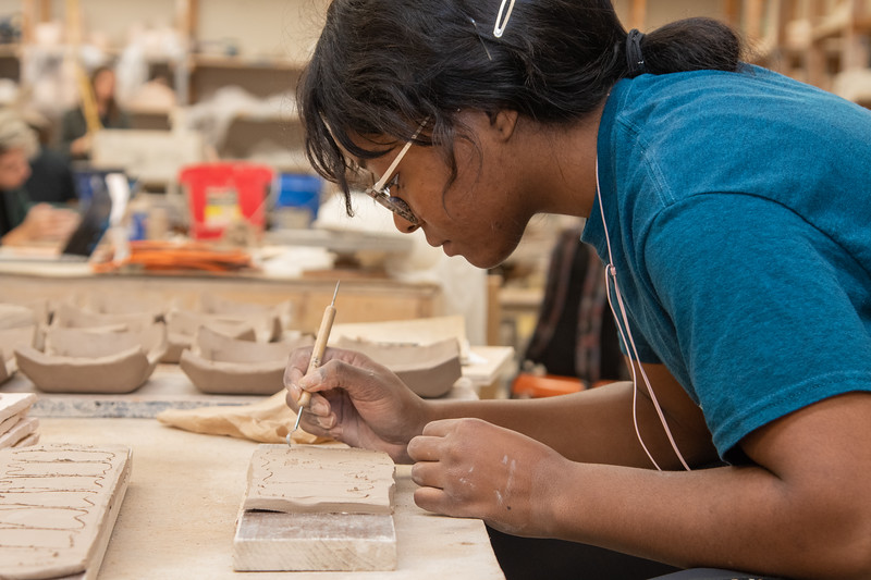 Christine Anusim working on her ceramic teeth ornaments in the Center for the Arts building.