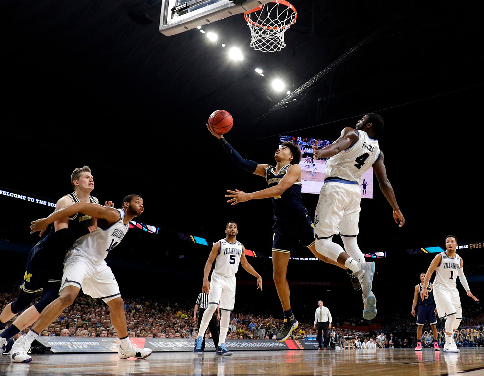 . Michigan guard Jordan Poole drives to the basket past Villanova forward Eric Paschall (4) during the first half in the championship game of the Final Four NCAA college basketball tournament, Monday, April 2, 2018, in San Antonio. (AP Photo/David J. Phillip)