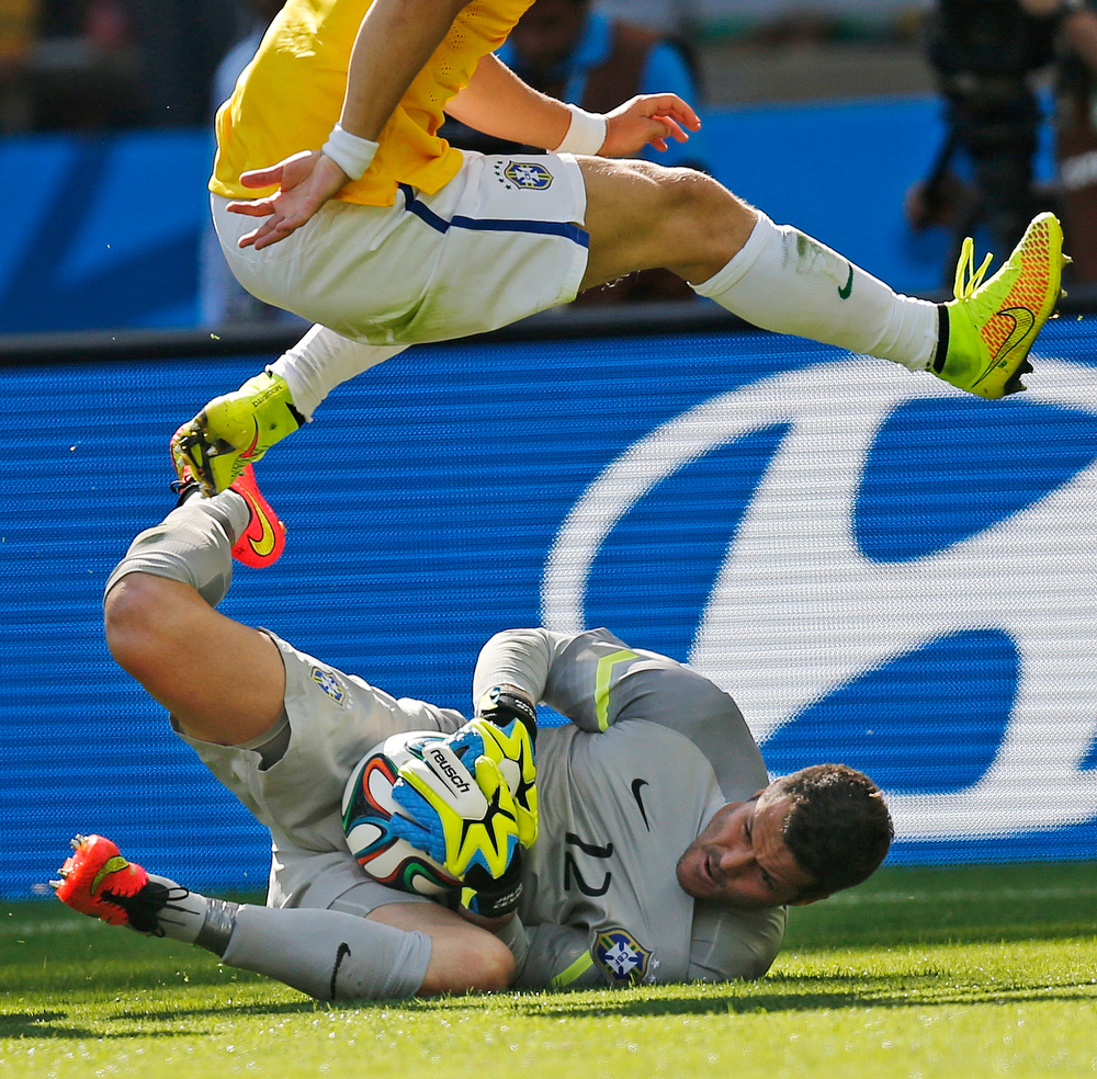 . Brazil\'s David Luiz jumps over Brazil\'s goalkeeper Julio Cesar during the World Cup round of 16 soccer match between Brazil and Chile at the Mineirao Stadium in Belo Horizonte, Brazil, Saturday, June 28, 2014. (AP Photo/Frank Augstein)