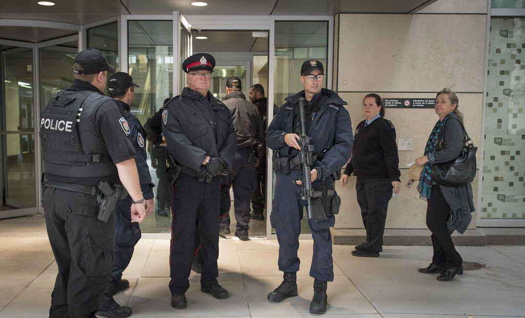 . Heavily armed police officers prepare to enter a building on the edge of a restricted zone in Ottawa, Ontario after multiple shootings on October 22, 2014. AFP PHOTO/Peter McCabe/AFP/Getty Images
