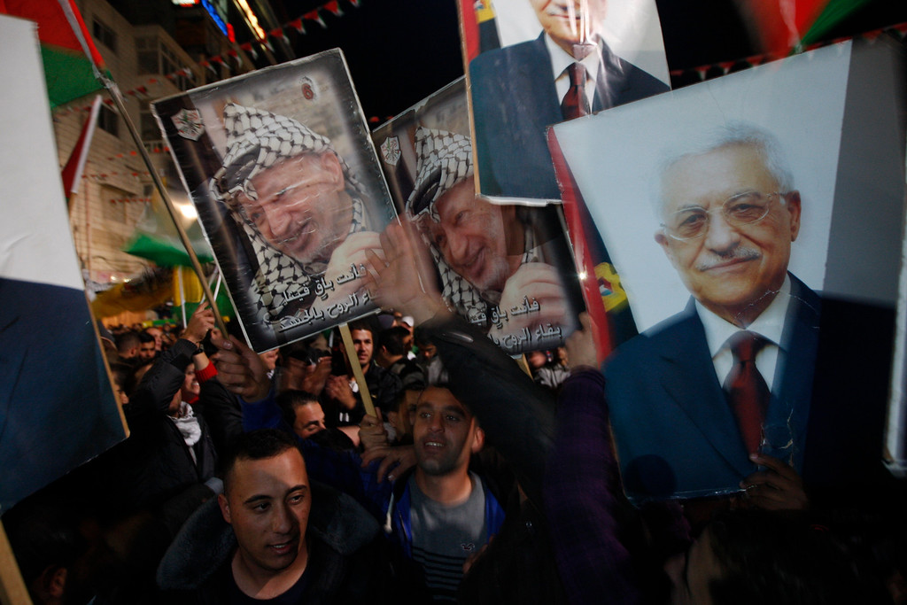 . Palestinians celebrate as they wave posters of former Palestinian leader Yasser Arafat, left, and President Mahmoud Abbas, right, as they watch the U.N. General Assembly votes on a resolution to upgrade the status of the Palestinian Authority to a nonmember observer state, in the west bank city of Ramallah, Thursday, Nov. 29, 2012.  The U.N. General Assembly has voted by a more than two-thirds majority to recognize the state of Palestine. The resolution upgrading the Palestinians\' status to a nonmember observer state at the United Nations was approved by the 193-member world body late Thursday by a vote of 138-9 with 41 abstentions. (AP Photo/Majdi Mohammed)