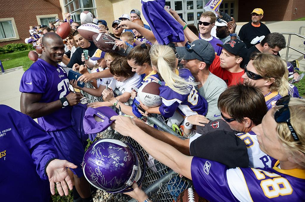 . Minnesota Vikings running back Adrian Peterson signs autographs at Vikings training camp in Mankato, Minn., on Friday, July 26, 2013. (Pioneer Press: Ben Garvin)