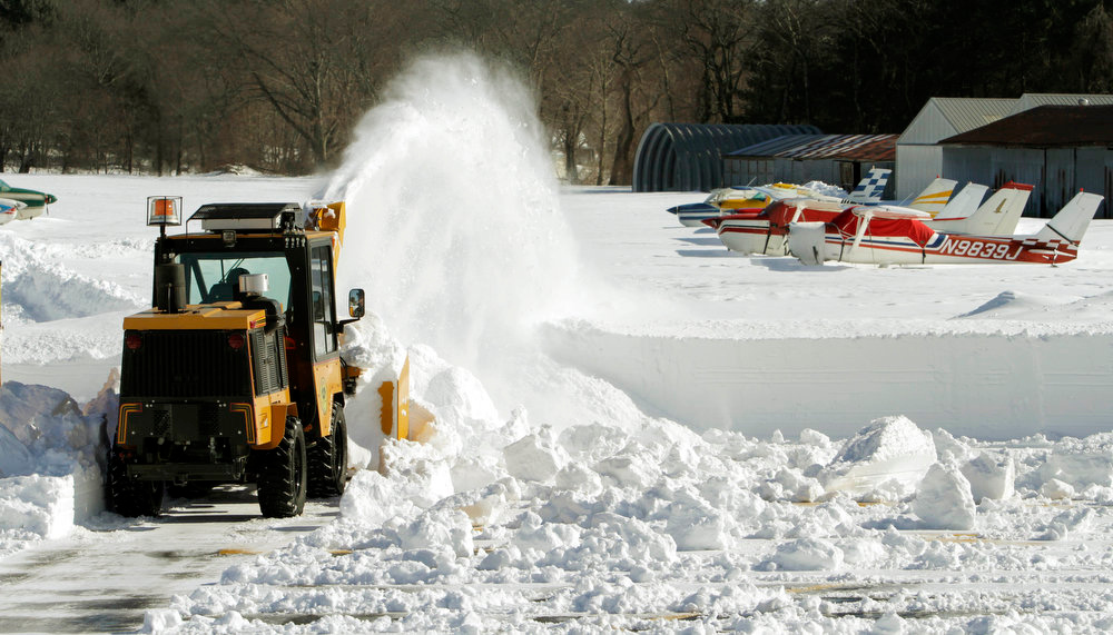 . Airport manager Bruce Prentiss operates a blowing machine to clear snow as planes are sit idle in Marlborough, Mass., Sunday, Feb. 10, 2013, after more than two feet of snow blanketed the region from a storm that ended Saturday.  (AP Photo/Bill Sikes)