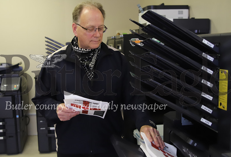 Rick McDeavitt pulls 'Praying for You' signs off of a printer at Hagan Business Machines in Butler Thursday. Volunteers from numerous religious denominations will be handing out the flyers for residents to display in their windows.  Local relgious leaders will be coming to the homes of those with signs hanging to offer outdoor prayers. Seb Foltz/Butler Eagle