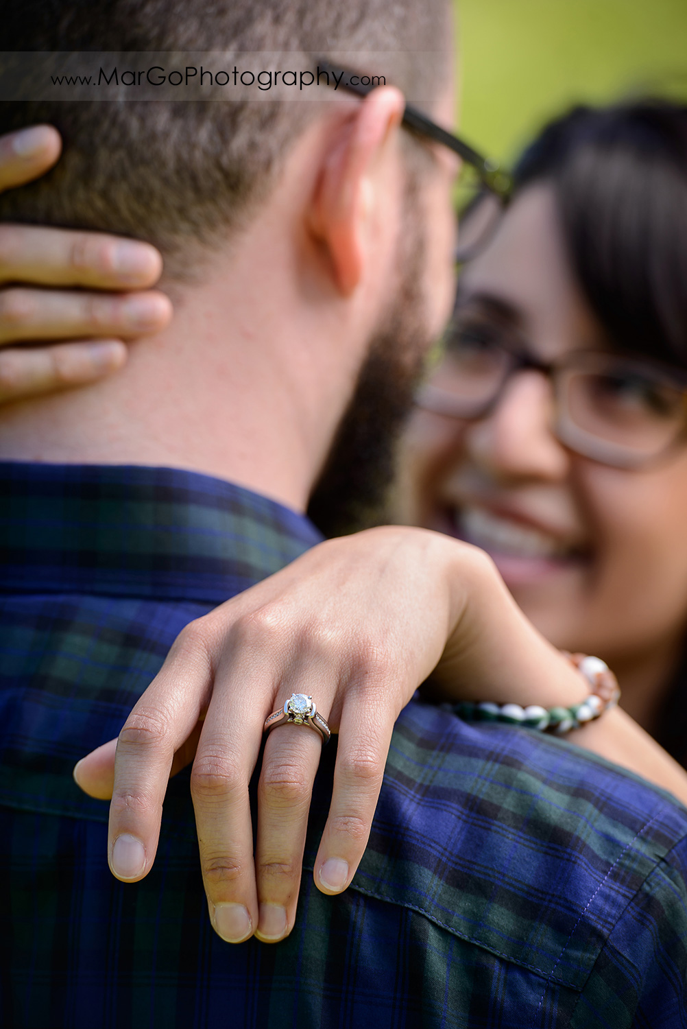 ring shot of man in blue shirt and woman in blue dress during engagement session at Sunol Regional Wilderness