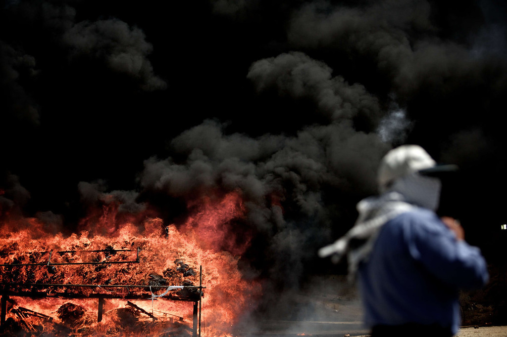 . An Iranian employee of the anti-drug police watches 50 tons of drugs seized in recent months burning in eastern Tehran on June 26, 2013 to mark the International Day Against Drug Abuse and Illicit Trafficking.  BEHROUZ MEHRI/AFP/Getty Images