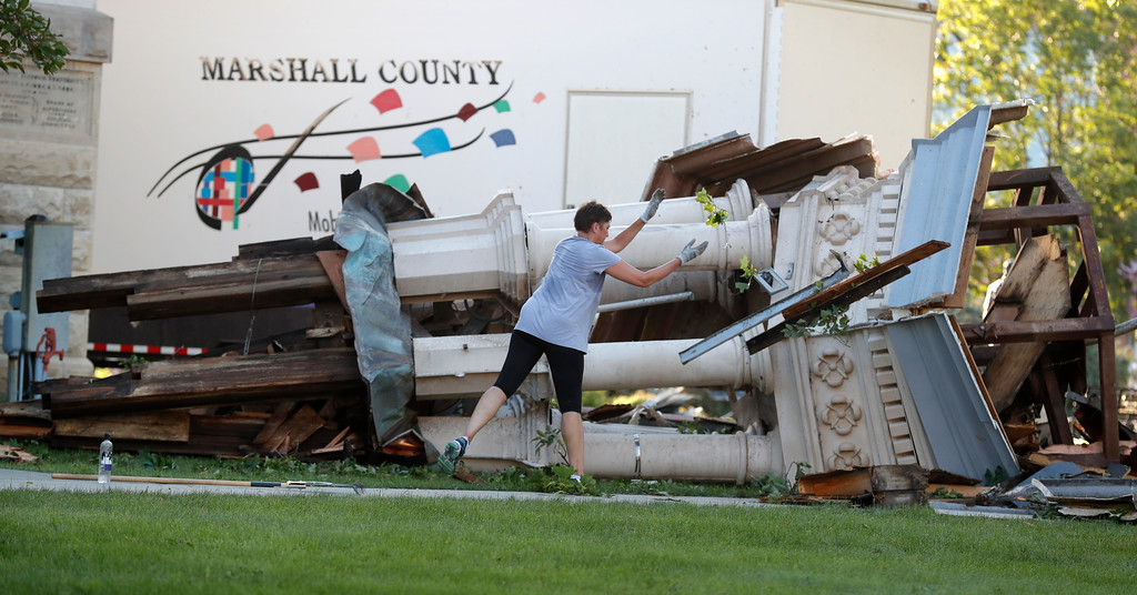 . A worker cleans up debris from the tornado damaged Marshall County Courthouse\'s tower Thursday, July 19, 2018, in Marshalltown, Iowa. Several buildings were damaged by a tornado in the main business district in town including the historic courthouse. (AP Photo/Charlie Neibergall)