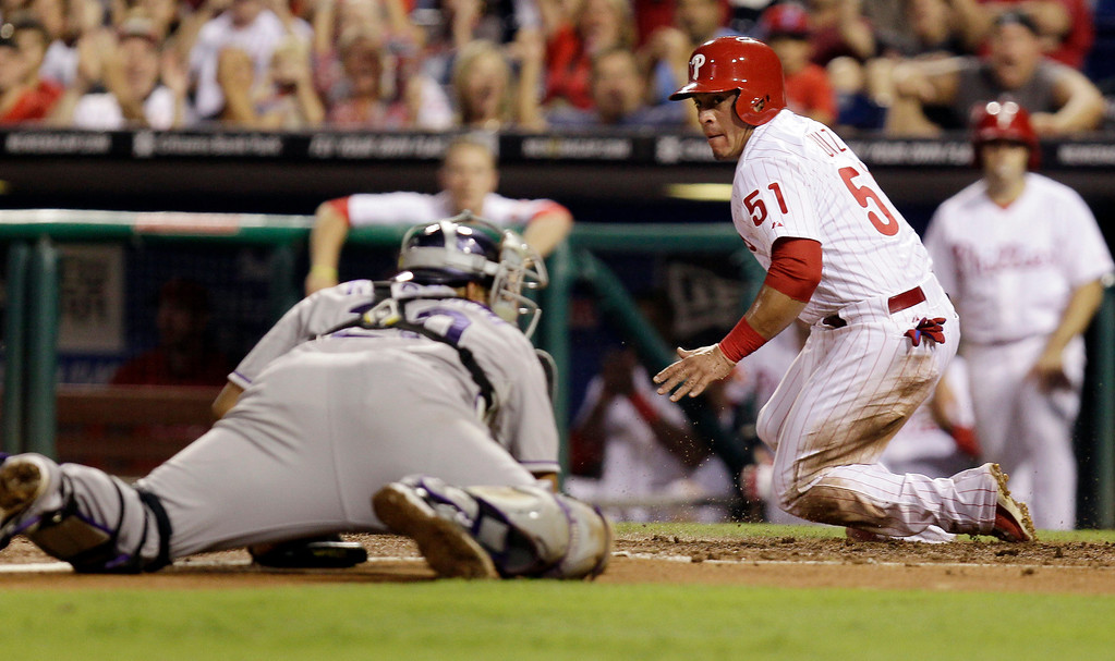 . Philadelphia Phillies\' Carlos Ruiz is safe at home on a sacrifice fly ball to center field by Domonic Brown before Colorado Rockies catcher Willin Rosario can make the tag in the third inning in a baseball game, Tuesday, Aug. 20, 2013, in Philadelphia. (AP Photo/Laurence Kesterson)