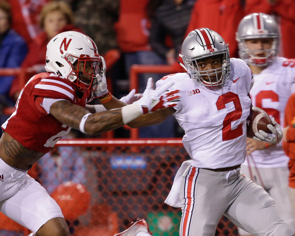 . Ohio State running back J.K. Dobbins (2) stiff-arms Nebraska defensive back Lamar Jackson (21) as he runs for a touchdown during the first half of an NCAA college football game in Lincoln, Neb., Saturday, Oct. 14, 2017. (AP Photo/Nati Harnik)